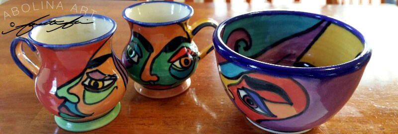 Stoneware mugs and bowl with bright colourful faces