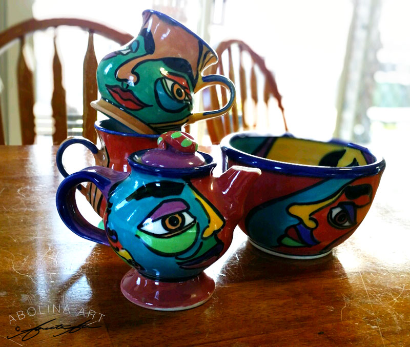 Teapot, mugs and a bowl from 'Faces' range